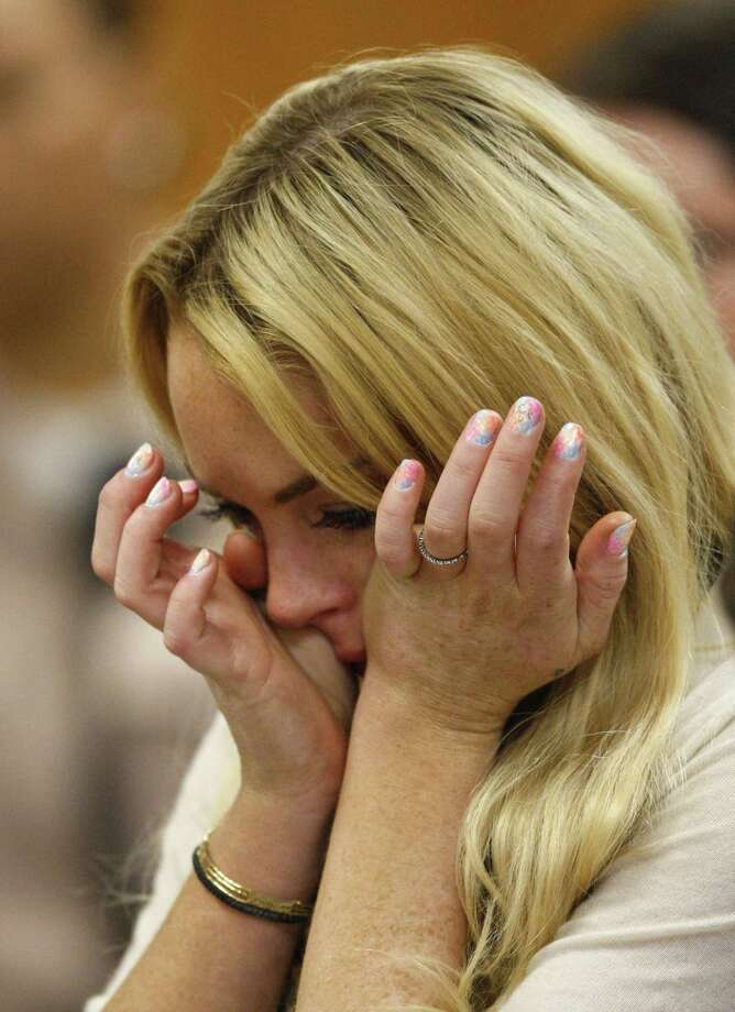 ** EDS NOTE: OBSCENE LANGUAGE ON LEFT MIDDLE FINGER NAIL ** Actress Lindsay Lohan reacts after the sentencing by Superior Court Judge Marsha Reve during a hearing in Beverly Hills, Calif., Tuesday, July 6, 2010. The judge sentenced Lindsay Lohan to 90 days in jail Tuesday after ruling she violated probation in a 2007 drug case by failing to attend court-ordered alcohol education classes. (AP Photo/David McNew, Pool) Photo: ASSOCIATED PRESS / Getty Images, POOL