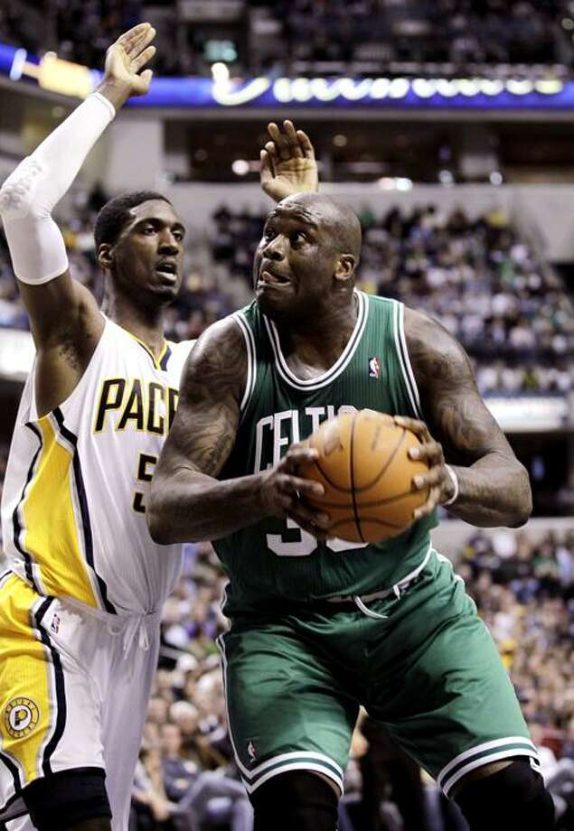 Boston Celtics center Shaquille O'Neal, right, shoots in front of Indiana Pacers center Roy Hibbert in the first half of an NBA basketball game in Indianapolis, Tuesday, Dec. 28, 2010.  (AP Photo/Michael Conroy)