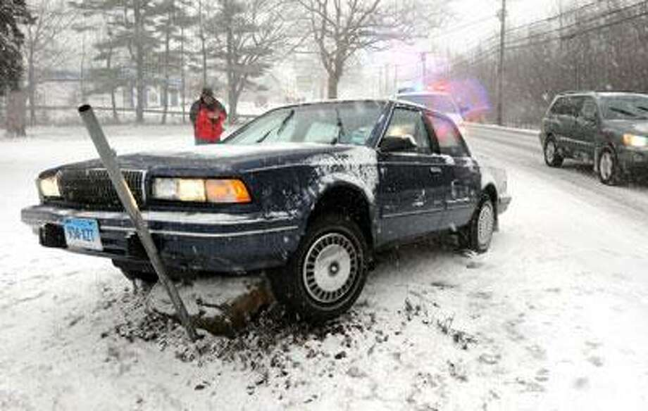A car rests on a pole after it slid off Route 1 in Clinton as road conditions worsened from the storm. (Mara Lavitt/Register)