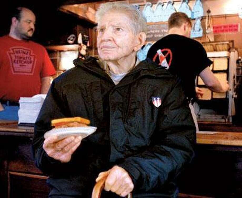 Ken Lassen, of Louie's Lunch, with one of their famous hamburgers. Lassen is defending Louie's title as purveyor of the first hamburger. (Melanie Stengel/Register)