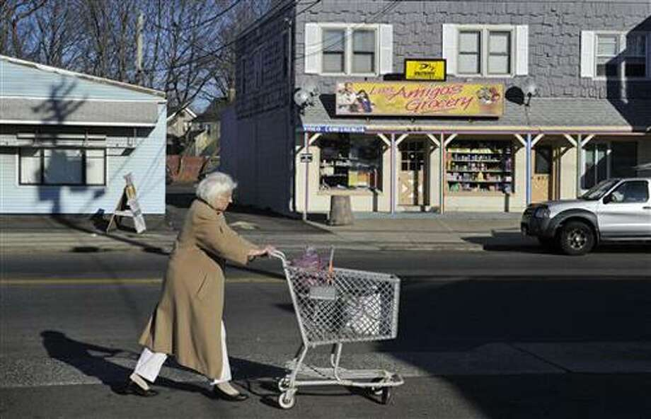 In this Wednesday, Dec. 22, 2010 photo, a woman pushes a shopping cart past Los Amigos Grocery in East Haven, Conn.  Luis Rodriguez, an immigrant from Ecuador and owner of the Los Amigos Grocery, said he was arrested two months ago and jailed for five days after a woman pointed out to police that his 3-year-old son was not supervised on the sidewalk outside the store. A federal civil rights investigation is under way and the FBI recently opened a criminal probe for allegations of racial profiling against Hispanics by East Haven police.  (AP Photo/Jessica Hill) Photo: AP / FR125654 AP