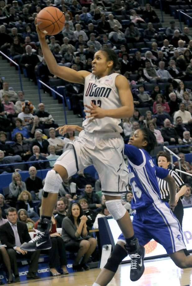 Connecticut's Maya Moore goes up for a one-handeer asa Seton Hal's Jazzmine Johnson tries  to guard her in the second half of an NCAA women's college basketball game in Hartford, Conn., Tuesday, Feb. 22, 2011.Connecticut defeated Seton Hall 80-59. (AP Photo/Bob Child)