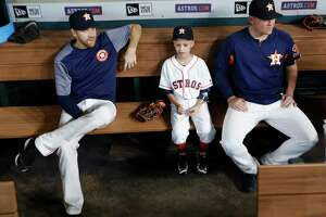Cameron Gooch, 9,sits in the dugout with Houston Astros relief pitcher Will Harris and Colin McHugh before the start of an MLB game at Minute Maid Park, Thursday, Aug. 17, 2017, in Houston. Cameron was participating in the Make-A-Wish program.
