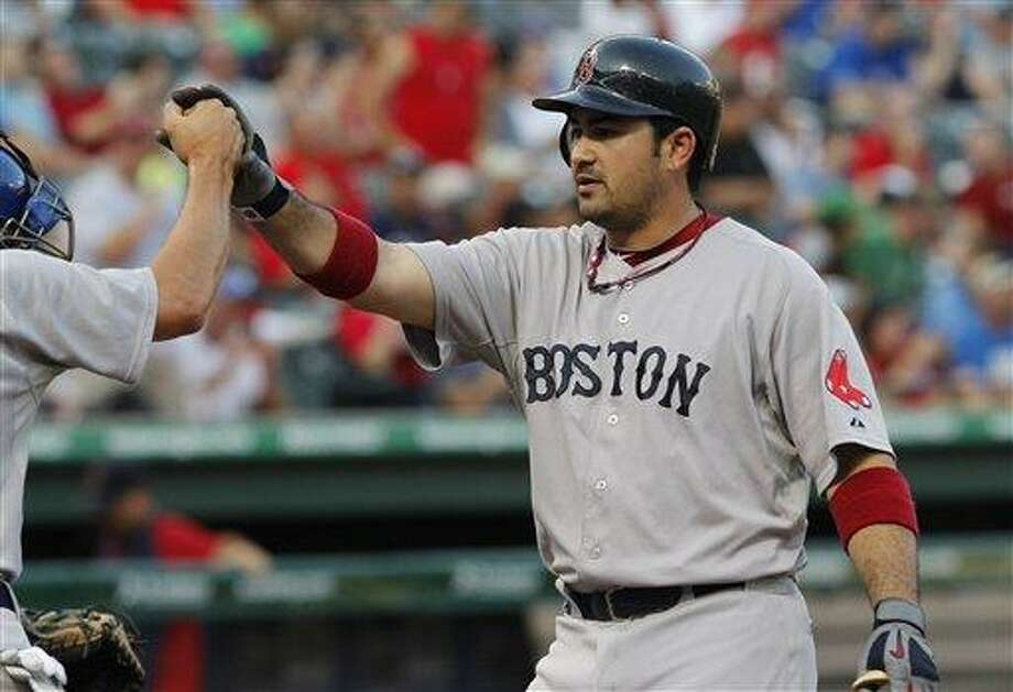 Boston Red Sox Adrian Gonzalez is met at home plate by teammates after hitting a two run homer in the first inning against the  Texas Rangers during the first inning of the baseball game in Arlington, Texas, Tuesday, Aug. 23, 2011. (AP Photo/LM Otero) Photo: ASSOCIATED PRESS / AP2011