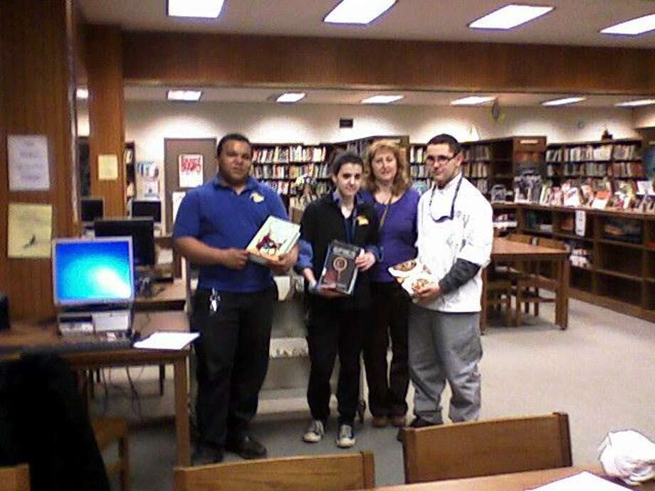 National Honor Society Adviser Cheryl Lee and Vinal Teach students show off some books. From left to right: Phil Masotta, Jacquelyn Sattler, Cheryl Lee, Evan Ducot.