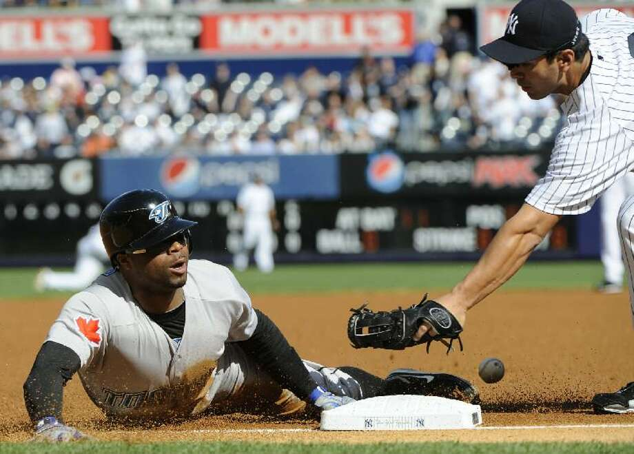 ASSOCIATED PRESS Toronto's Rajai Davis, left, slides into third base with a triple as New York Yankees third baseman Eric Chavez cannot handle the throw during the first inning of Saturday's game at Yankee Stadium in New York. The Yankees beat the Blue Jays 5-4.