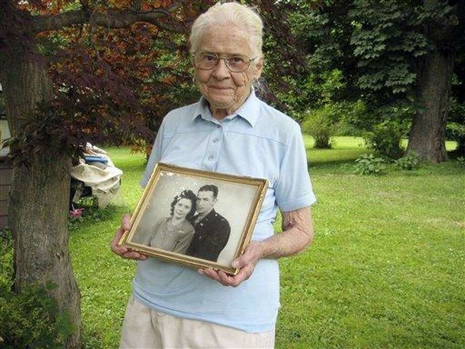 In This June 25 photo, Jean Stevens, 91, holds a photograph from the 1940s of herself and her late husband, James, outside her home in Wyalusing, Pa. Authorities say Stevens stored the bodies of her husband, who died in 1999, and her twin, who died in October 2009, on her property. As state police finish their investigation into a singularly macabre case, no charges have been filed, Stevens wishes she could be reunited with James Stevens, her husband of nearly 60 years, and June Stevens, her twin. But their bodies are with the Bradford County coroner now, off-limits to the woman who loved them best. (AP) Photo: AP / AP