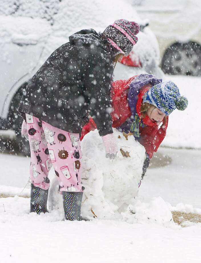 Eleven-year-old twins, Cameron and Danielle Whitlock, make a snowman in their front yard in Decatur, Ala. on an unusually snowy Christmas morning, Saturday, Dec. 25, 2010. After blanketing parts of the Midwest and hampering motorists there on Christmas Eve, the storm dipped south late Friday. Winter weather advisories were in effect Saturday morning from Arkansas to the Carolinas and from West Virginia to central Alabama. Much of North Carolina was under a winter storm warning. (AP Photo/The Decatur Daily, John Godbey) Photo: ASSOCIATED PRESS / AP2010