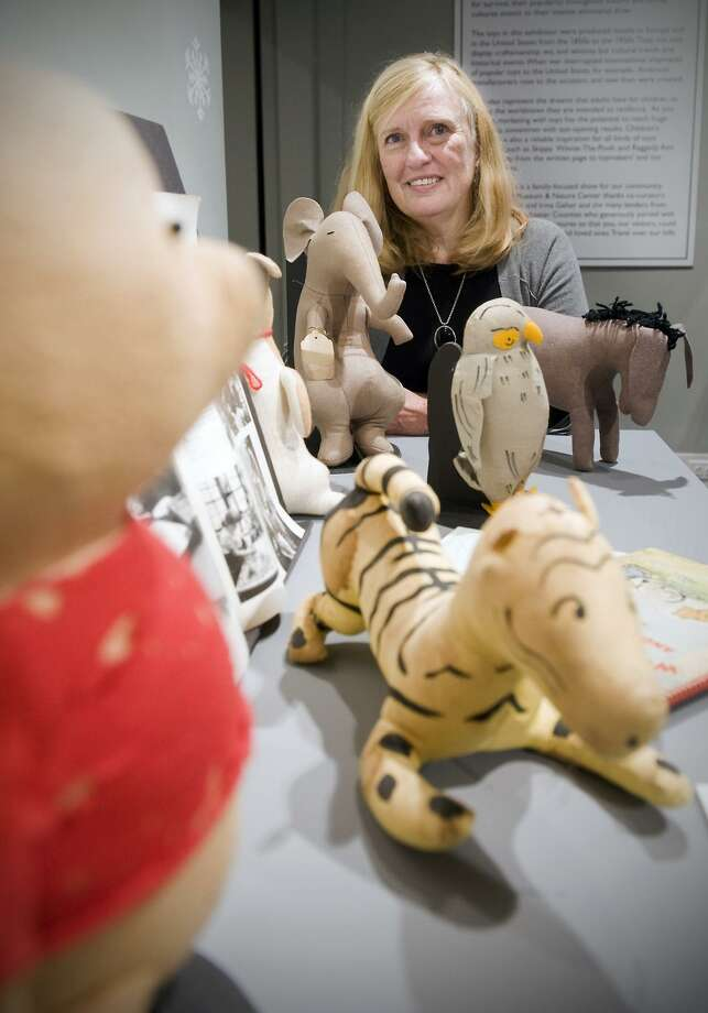 "Joyce Riemer looks through her mother Agnes Brush's collection of Winnie the Pooh stuffed animals and books at the Stamford Museum and Nature Center's exhibit ""Dolls, Toys and Teddy Bears"" in Stamford on Dec. 9. (AP Photo/Stamford Advocate, Kathleen O'Rourke) Photo: AP / Stamford Advocate"