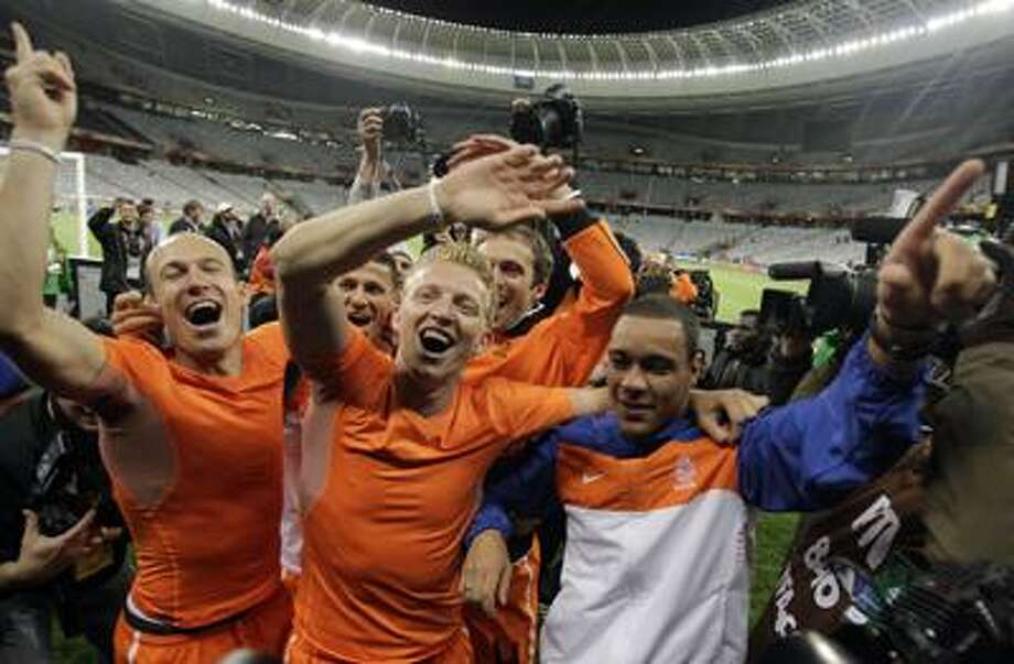 Netherlands players Arjen Robben, left, Dirk Kuyt, center, and Netherlands' Ibrahim Afellay, right, celebrate with other teammates at the end of the World Cup semifinal soccer match between Uruguay and the Netherlands at the Green Point stadium in Cape Town, South Africa, Tuesday. (AP) Photo: ASSOCIATED PRESS / AP