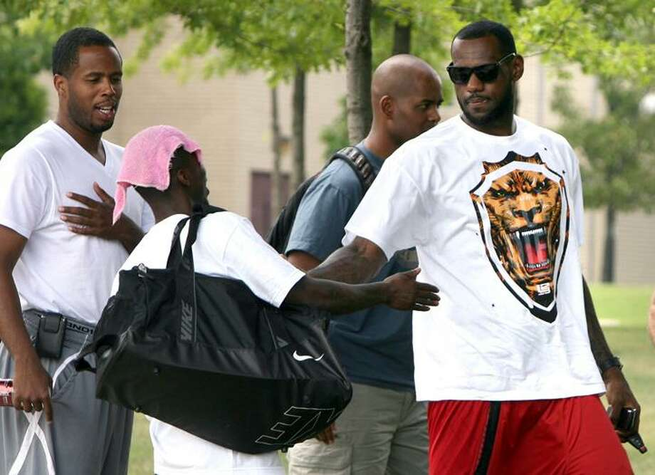 LeBron James, right, and Damon Jones, left,  arrive at the James A. Rhodes Arena for the LeBron James Skills Academy on Tuesday in Akron, Ohio.  James met with six teams last week, including the Cavaliers and Chicago Bulls, who are believed to be the front-runners to sign him. Other teams could be positioning themselves to make another run after making their initial presentations.  (AP Photo/The Plain Dealer, Chuck Crow) Photo: AP / The Plain Dealer