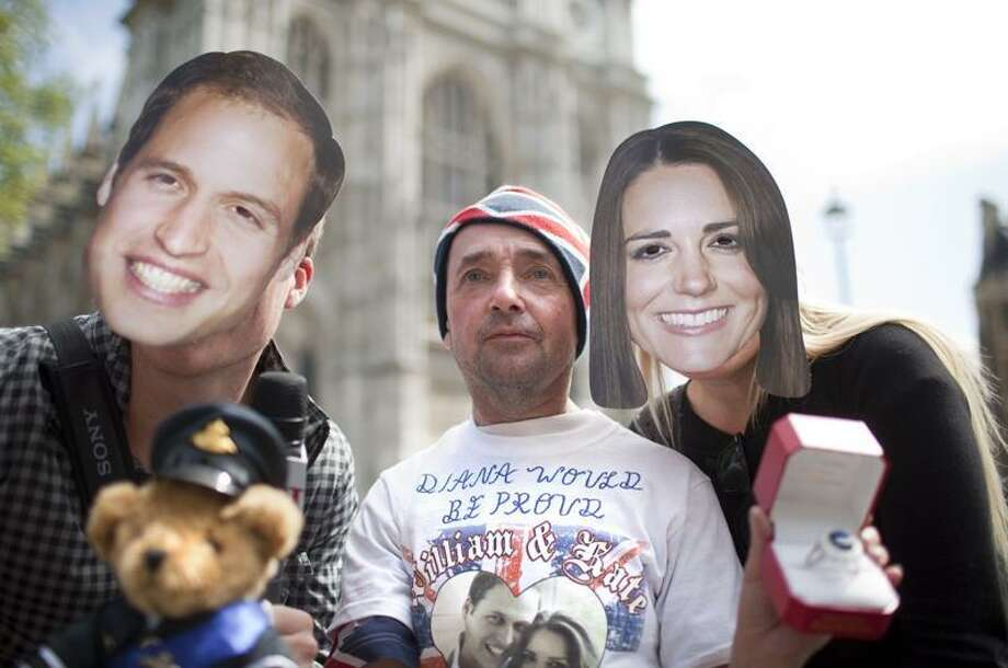 John Loughrey, center, a royal fan from south London, poses with Australian Angus Oloughlin, left, and Renee Peterson as they wear masks with the faces of Britain's Prince William and his fiancee, Kate Middleton, in front of Westminster Abbey in London Wednesday. Associated Press Photo: AP / AP