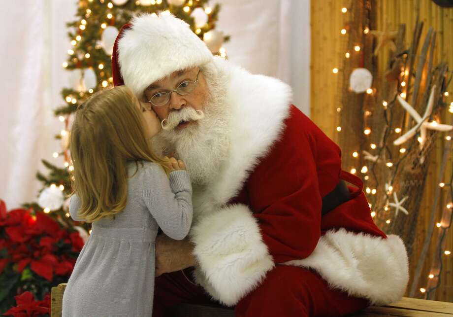 "In this Nov. 30 photo, Santa, Cliff Snider, gets a kiss on the cheek from Bella Champion, 3, during a Christmas photo shoot at the ""Beach Shack"" in Emerald Isle, N.C. When Snider, who's been playing Santa since he was a teenager, gets a big-ticket request, he typically answers: ""There's an awful lot of children asking for that this year. What else do you want?""     (AP Photo/Tom Copeland) Photo: ASSOCIATED PRESS / AP2011"