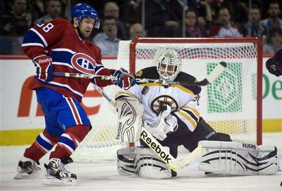 Boston Bruins goaltender Tim Thomas makes a save next to Montreal Canadiens' David Desharnais (58) during the third period in Game 3 of an NHL hockey Stanley Cup playoffs first-round series, Monday, April 18, 2011, in Montreal. Boston won 4-2. (AP Photo/The Canadian Press, Graham Hughes) Photo: AP / The Canadian Press