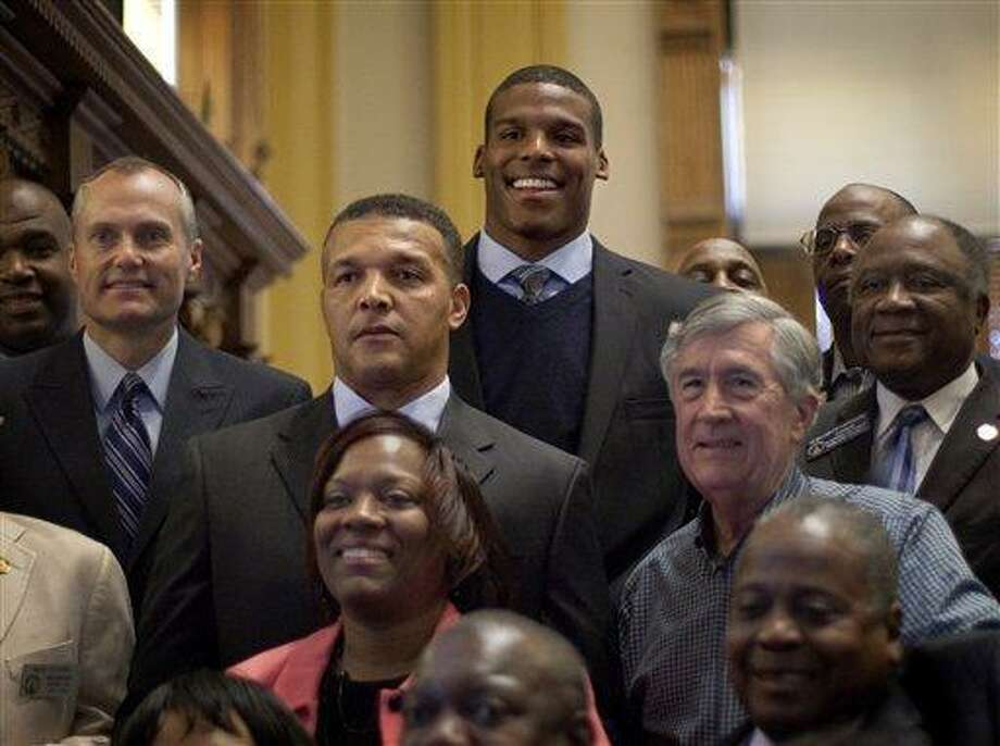 Heisman Trophy winner Cam Newton, top, stands behind his father Cecil, center and mother Jackie, bottom center, following a ceremony recognizing the former Auburn University quarterback in the Georgia Legislature Friday, April 1, 2011 in Atlanta. (AP Photo/David Goldman) Photo: AP / AP