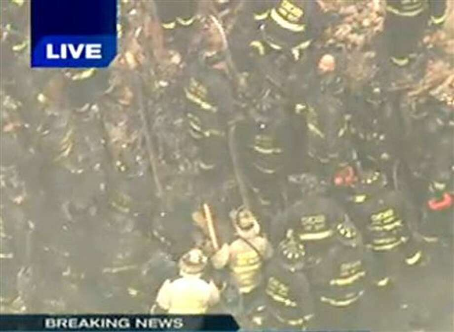 In this frame grab made from WGN-TV, Chicago firefighters work to save firefighters that were trapped when a wall collapsed Wednesday Dec. 22, 2010 in Chicago's South Side while they were fighting a blaze at an abandoned commercial building. Fire Media Affairs Director Larry Langford confirmed that firefighters were unaccounted for at the scene on Chicago's South Side and that rescue crews were working to save them. (AP Photo/Courtesy WGN-TV) MANDATORY CREDIT. NO SALES Photo: AP / WGN-TV