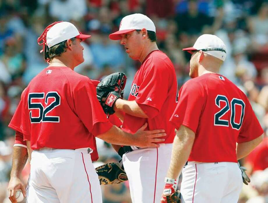 Boston Red Sox pitching coach John Farrell (52) talks with John Lackey, center, as Kevin Youkilis (20) looks on in the fourth inning of a baseball game Sunday in Boston. The Orioles won 6-1. (AP Photo/Michael Dwyer) Photo: AP / AP
