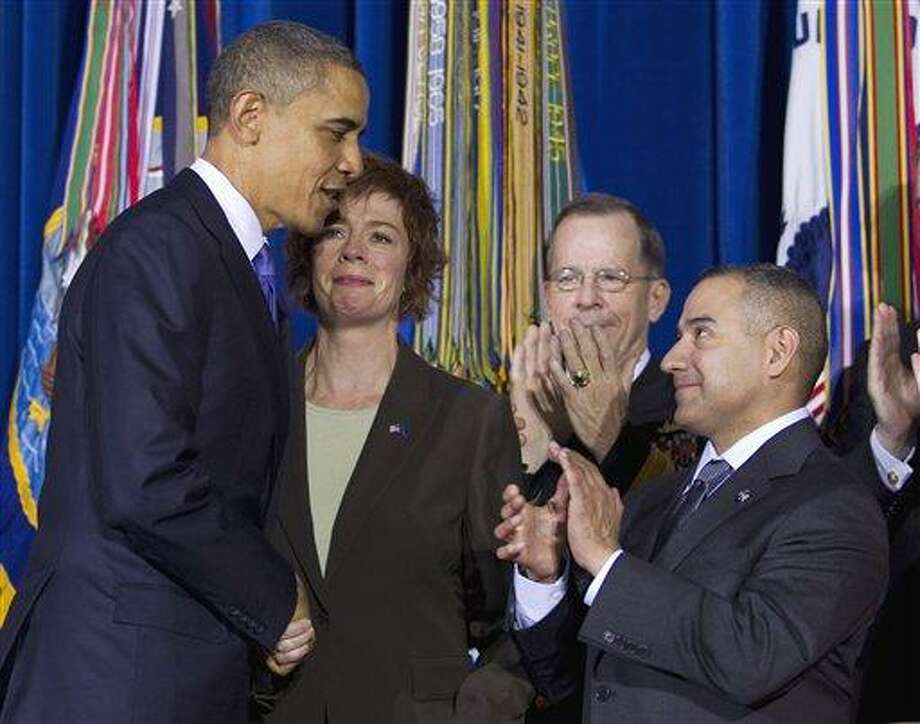 "President Barack Obama shakes hands with former Navy Commander Zoe Dunning, as Joint Chiefs Chairman Adm. Mike Mullen, second from right, and former Marine Staff Sgt. Eric Alva applaud during a signing ceremony for  ""don't ask, don't tell"" repeal legislation that would allow gays to serve openly in the military, Wednesday, Dec. 22, 2010, at the Interior Department in Washington.  (AP Photo/Evan Vucci) Photo: AP / AP"