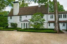 The white brick and board and batten 1929 colonial house at 501 Mine Hill Road sits on a 2.39-acre level corner lot in Greenfield Hill.