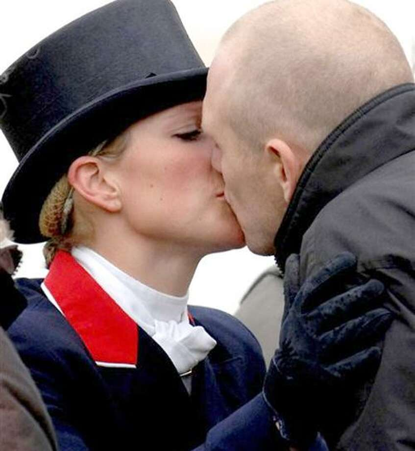 FILE -  In this file photo of May 4, 2007 Zara Phillips and boyfriend Mike Tindall kiss at the Badminton Horse Trials, Badminton, England. Buckingham Palace says Queen Elizabeth II's granddaughter Zara Phillips is engaged to her long-term boyfriend Mike Tindall. The palace said Tuesday Dec. 21, 2010 that 29-year-old Phillips, who is 12th in line to the throne, had accepted a proposal from rugby player Tindall. Phillips is the daughter of Princess Anne and her ex husband Capt. Mark Phillips, and the queen's eldest granddaughter. She has a successful career as an equestrian. (AP Photo/Barry Batchelor/PA Wire) UNITED KINGDOM OUT NO SALES NO ARCHIVE Photo: AP / PA