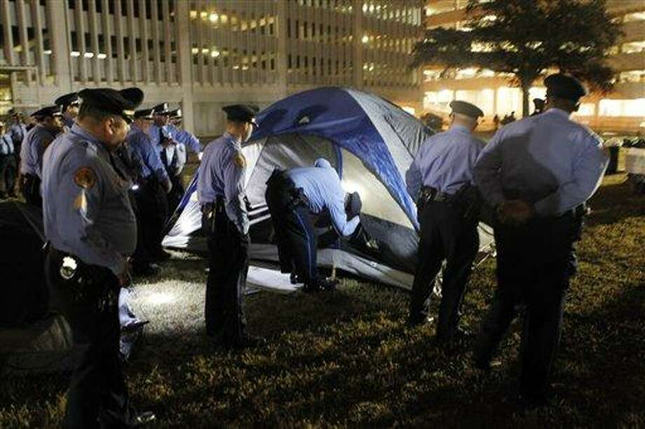 New Orleans police search inside tents for people as they clear out the Occupy New Orleans encampment in Duncan Plaza across from City Hall in New Orleans on Tuesday, Dec. 6, 2011. (AP Photo/Gerald Herbert) Photo: ASSOCIATED PRESS / AP2011