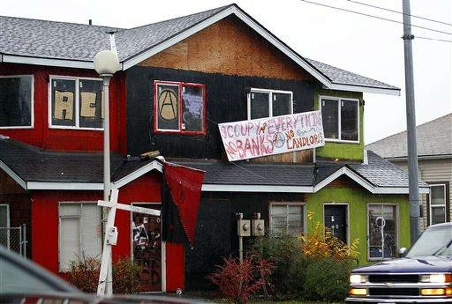 In this photo taken Nov. 22, 2011, a formerly boarded-up duplex that protesters have taken over in Seattle's Central District is seen. To protest foreclosures in the nation's housing market, Occupy Wall Street demonstrators in Seattle, Portland and Oakland have taken up a new tactic: Squatting in vacant properties. (AP Photo/Elaine Thompson) Photo: AP / AP