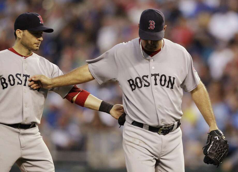 Boston Red Sox starting pitcher Tim Wakefield, right, and shortstop Marco Scutaro exchange support as Wakefield is replaced during the sixth inning of a baseball game against the Kansas City Royals in Kansas City, Mo., Saturday, Aug. 20, 2011. (AP Photo/Orlin Wagner) Photo: ASSOCIATED PRESS / AP2011