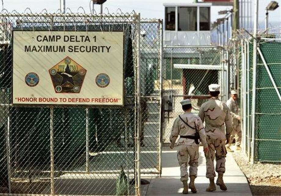 """FILE - In this file photo made June 27, 2006, reviewed by a U.S. Department of Defense official, U.S. military guards walk within Camp Delta military-run prison, at the Guantanamo Bay U.S. Naval Base, Cuba. Secret documents about detainees at the Guantanamo Bay prison reveal new information about some of the men that the United States believes to be terrorists, according to reports about the files released Sunday, April 24, 2011, by several American and European newspapers. The U.S. government criticized the publication as """"unfortunate."""" (AP Photo/Brennan Linsley, File) Photo: AP / AP2011"""