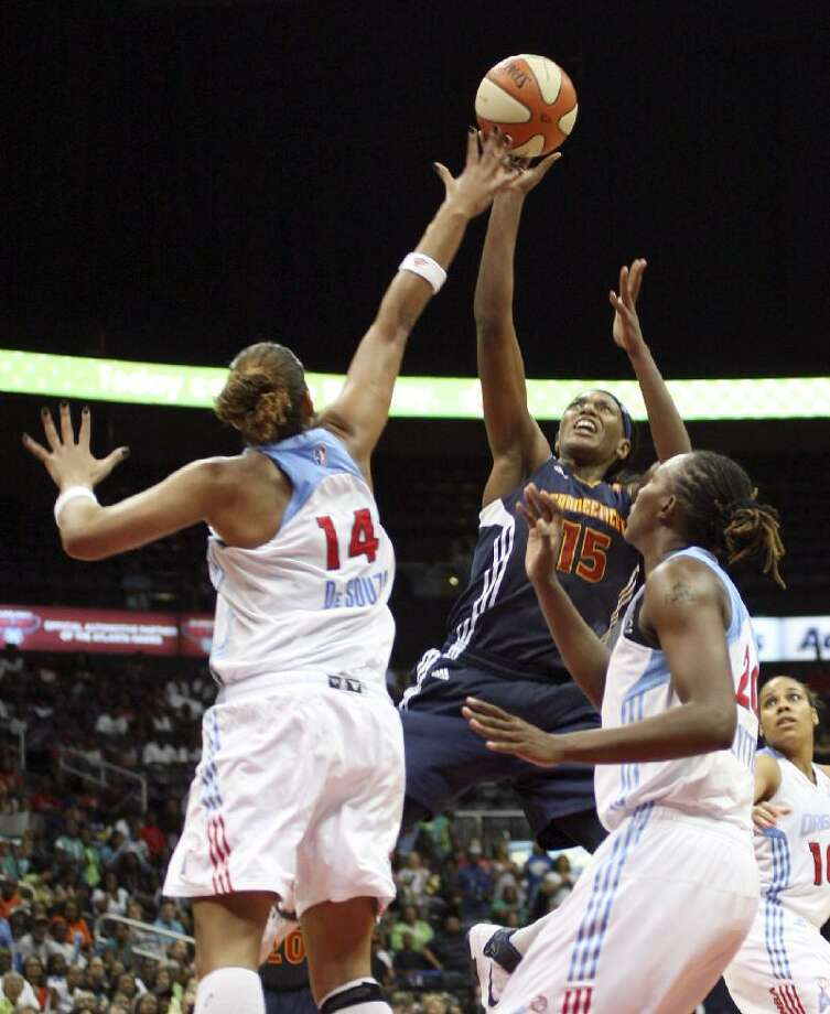 ASSOCIATED PRESS Connecticut Sun forward Asjha Jones, center, shoots between Atlanta Dream center Erika de Souza, left, and forward Sancho Lyttle in the second half of Friday's WNBA game in Atlanta. The Dream won 94-88 in overtime.