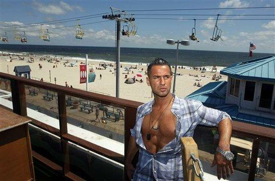 "Mike ""The Situation"" Sorrentino, cast member of MTV's ""Jersey Shore"" stands on a deck overlooking the boardwalk and beach at the home for the show Thursday, Aug. 4, 2011, in Seaside Heights, N.J. The cast members had fun in Italy, but they're glad to get back to their home facing the surf and sand of the real Jersey shore. The young partiers traveled to Florence, Italy, to film the fourth season, which premiers Thursday night. (AP Photo/Mel Evans) Photo: AP / AP"
