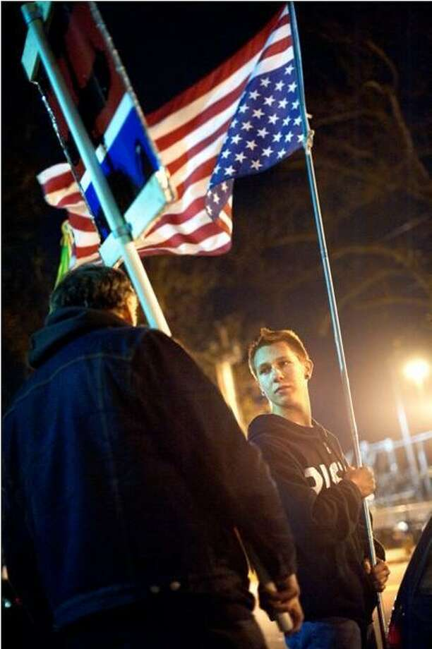 Cody Butler (facing camera, with upside-down flag) talks to Ray Neal in front of police headquarters at 1 Union Ave. while protesting the arrest of a fellow protester. VM Williams/Register