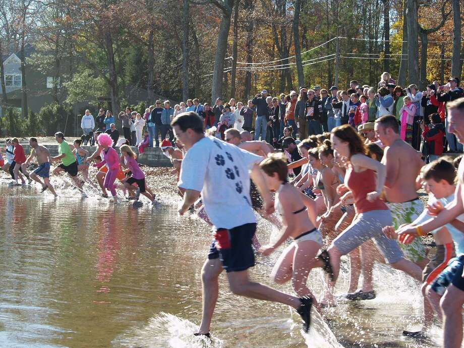 Tom Crean, 2010 East Hampton Turkey Plunge co-chair, leads over 60 participants into the chilly waters of Lake Pocotopaug.