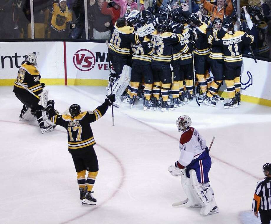 ASSOCIATED PRESS Montreal Canadiens goalie Carey Price, bottom right, skates off the ice as the Boston Bruins surround Nathan Horton after he scored the game-winning goal during the second overtime period in Game 5 of a first-round NHL Stanley Cup playoff series in Boston Saturday. The Bruins won 3-2 and took a 3-2 lead in the series.