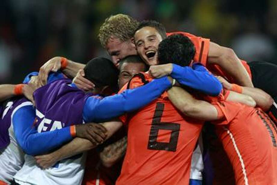 Netherlands' players including Ibrahim Afellay, top right, and Dirk Kuyt, center top, celebrate at the end of the World Cup quarterfinal soccer match between the Netherlands and Brazil at Nelson Mandela Bay Stadium in Port Elizabeth, South Africa, Friday. (AP) Photo: ASSOCIATED PRESS / AP