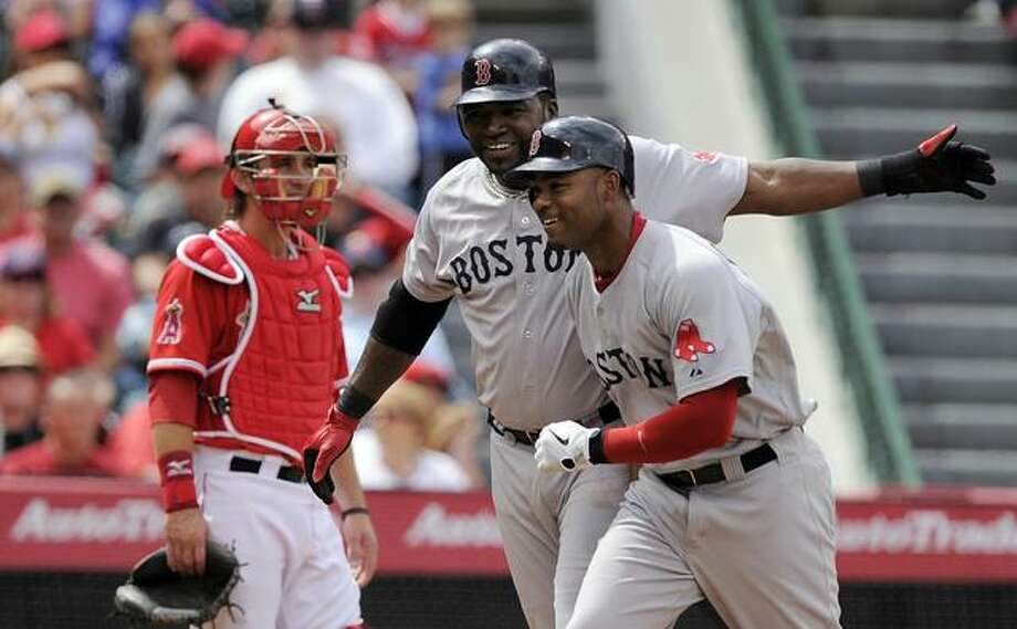 Boston Red Sox's David Ortiz, center, congratulates Carl Crawford after hitting a two-run home run as Los Angeles Angels catcher Jeff Mathis looks on during the sixth inning of their Major League Baseball game, Sunday, April 24, 2011, in Anaheim, Calif. (AP Photo/Mark J. Terrill) Photo: ASSOCIATED PRESS / AP2011