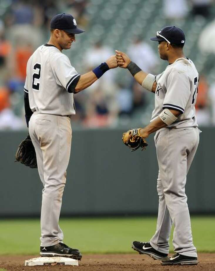 New York Yankees' Derek Jeter, left, and Robinson Cano celebrate their 6-3 win over the Baltimore Orioles in 11 innings of a baseball game, Sunday, April 24, 2011 in Baltimore. (AP Photo/Gail Burton) Photo: ASSOCIATED PRESS / AP2011