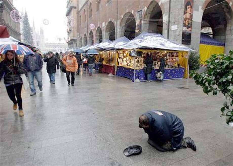 In this photo taken on Friday, Dec. 17, 2010, a beggar asks for coins near an open air Christmas market in Milan, Italy. This Christmas, Europeans are hunkering down to an uncertain future, as a debt crisis that erupted two years ago in Greece flares anew in Ireland, and has quickly threatened to engulf Portugal, Spain, and Italy. (AP Photo/Luca Bruno) Photo: AP / AP