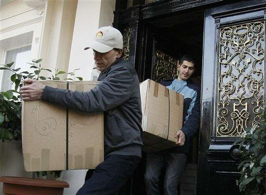 Removal men carry packages Friday from what is believed to be the residence of Iranian diplomats into a removal lorry in London. Britain ordered Iranian diplomats off its soil, pulled its diplomats out of Iran and backed new sanctions on the Islamic republic after Iranian protesters stormed and ransacked the U.K. embassy compounds in Tehran on Tuesday. Associated Press Photo: AP / AP