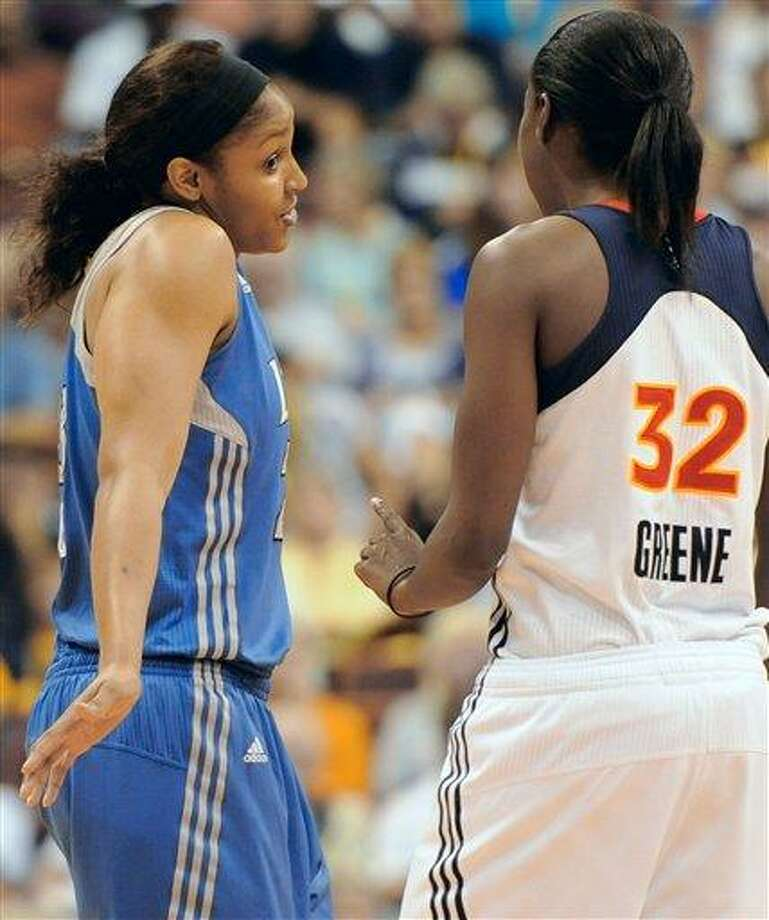 Minnesota Lynx' Maya Moore, left gestures toward former University of Connecticut teammate and current Connecticut Sun Kalana Greene,  right, before tip-off in a WNBA basketball game in Uncasville Tuesday. Moore scored only 2 points as the Sun won 108-79. (AP photo) Photo: AP / AP2011