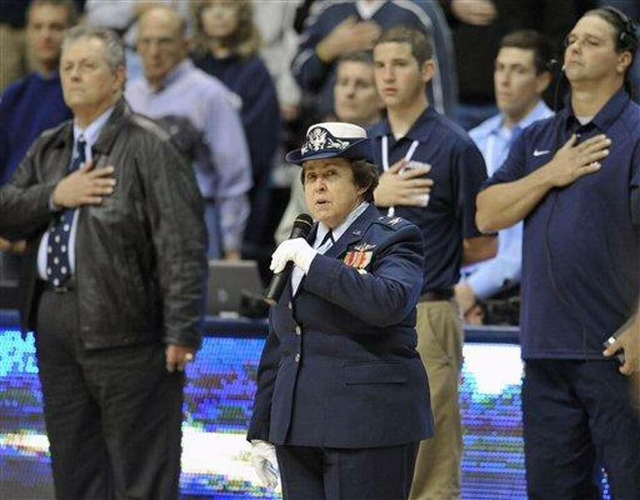 In this Sunday, Nov. 13, 2011 photo, Linda Schwartz, the commissioner of Connecticut's Department of Veterans Affairs, leads the Pledge of Allegiance before an NCAA college basketball game between Connecticut and Holy Cross in Storrs, Conn.  Connecticut women's basketball coach Geno Auriemma can't remember saying the Pledge of Allegiance out loud since the day he became a United States' citizen in 1994.  But Auriemma, a native of Italy who moved to the United States as a child, and everyone else attending UConn basketball and football games this season has been asked to put hand over heart and recite those familiar words just before the national anthem is played. (AP Photo/Jessica Hill) Photo: AP / AP2011