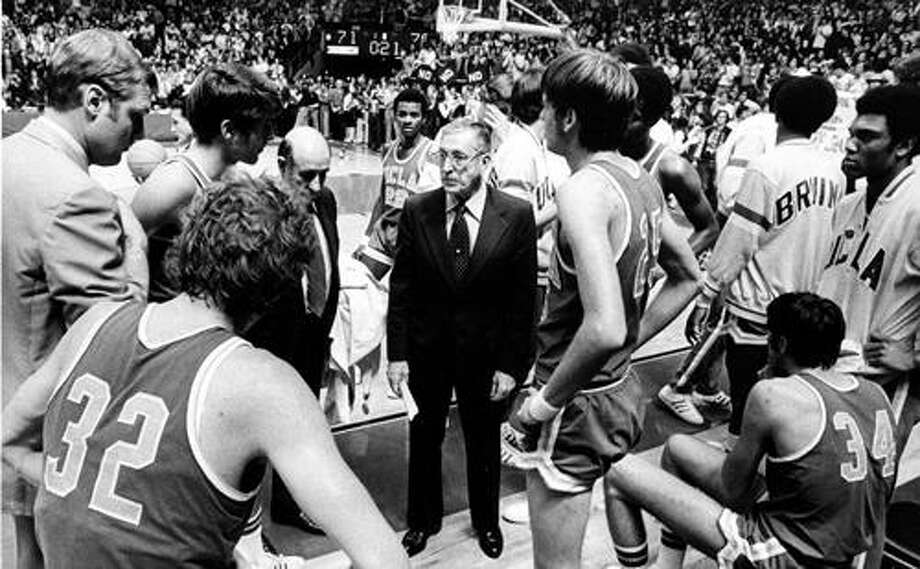 FILE - This Jan. 19, 1974, file photo shows UCLA basketball coach John Wooden, center,  during the last time out against Notre Dame, in South Bend, Ind. At left foreground is Bill Walton (32). The date the streak ended is burned in Walton's memory. He spits it out with distaste when asked what he recalls most about UCLA's NCAA-record 88-game winning streak.  (AP Photo/File) Photo: ASSOCIATED PRESS / AP1974