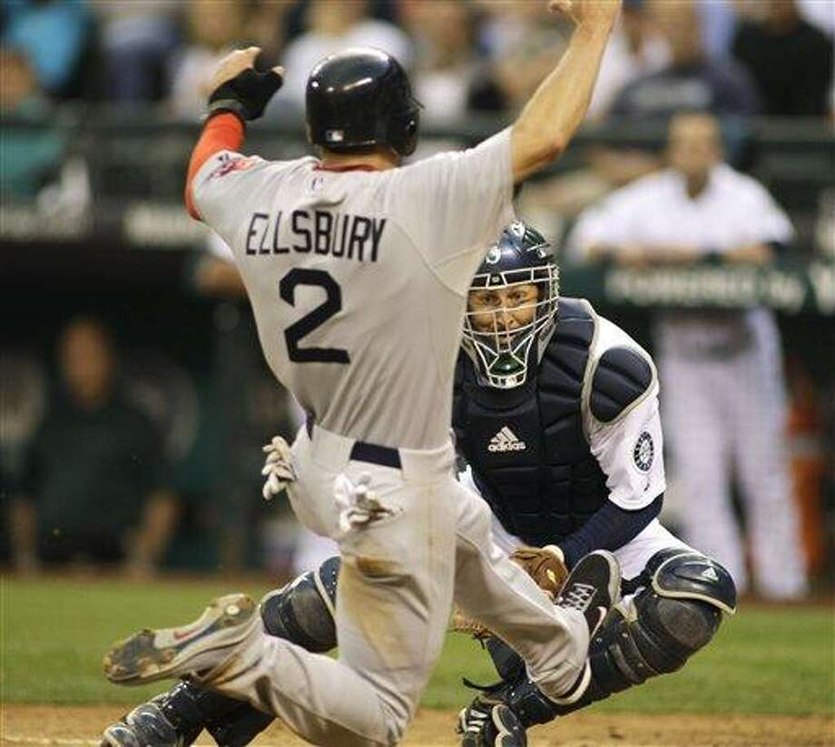 Boston Red Sox' Jacoby Ellsbury is eyed by Seattle Mariners catcher Josh Bard before Bard tagged him out at home in the fourth inning of a baseball game, Saturday, Aug. 13, 2011, Seattle. An argument over the call at the plate led to the ejection of Red Sox manager Terry Francona. (AP Photo/Ted S. Warren) Photo: ASSOCIATED PRESS / AP2011