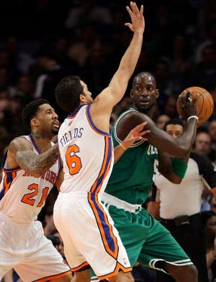 Boston Celtics' Kevin Garnett (5) protects the ball from New York Knicks' Landry Fields (6) and Wilson Chandler (21) during the first half of Wednesday's game in New York. (AP Photo)