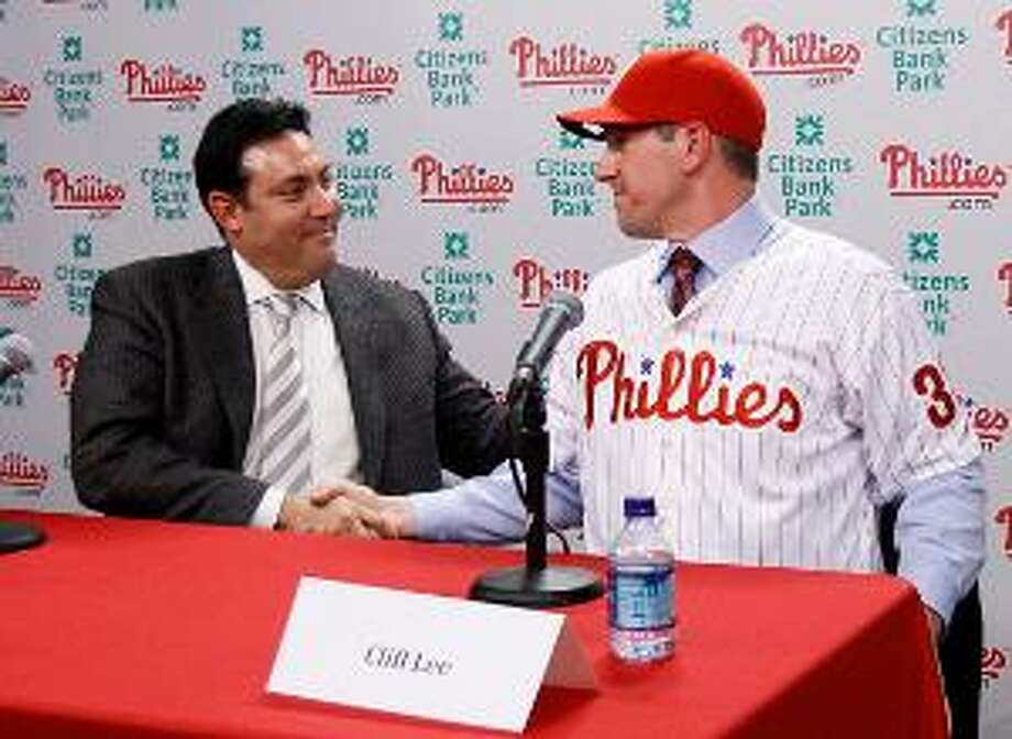 Philadelphia Phillies general manager Ruben Amaro Jr., left, and pitcher Cliff Lee shake hands after a news conference, Wednesday, in Philadelphia. Lee and the Phillies finalized a $120 million, five-year contract that brings the star pitcher back to Philadelphia. (AP Photo)