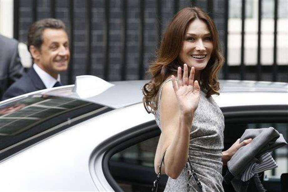 "FILE - In this  Friday, June 18, 2010 file photo, Carla Bruni-Sarkozy, right, waves as she leaves 10 Downing Street in London with her husband French President Nicolas Sarkozy, left, after their lunch with British Prime Minister, David Cameron and his wife Samantha Cameron. Iran's hardline media have called the French first lady a ""prostitute"" after she expressed strong support for an Iranian woman facing death by stoning for adultery. (AP Photo/Sang Tan, File) Photo: AP / AP"