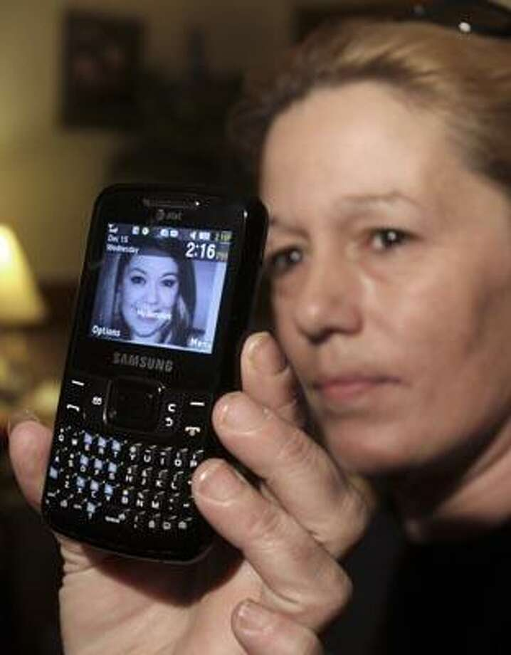 Lorraine Ela, of South Portland, Maine, displays her cell phone that has a picture of her missing daughter, while being interviewed by the media at her home on Wednesday, Dec. 15, 2010.  Ela's daughter, Megan Waterman, 22,  has been missing since June and authorities say they are trying to determine whether she is one four women's bodies found along a remote beach highway on New York's Long Island. (AP Photo/Pat Wellenbach) Photo: AP / AP