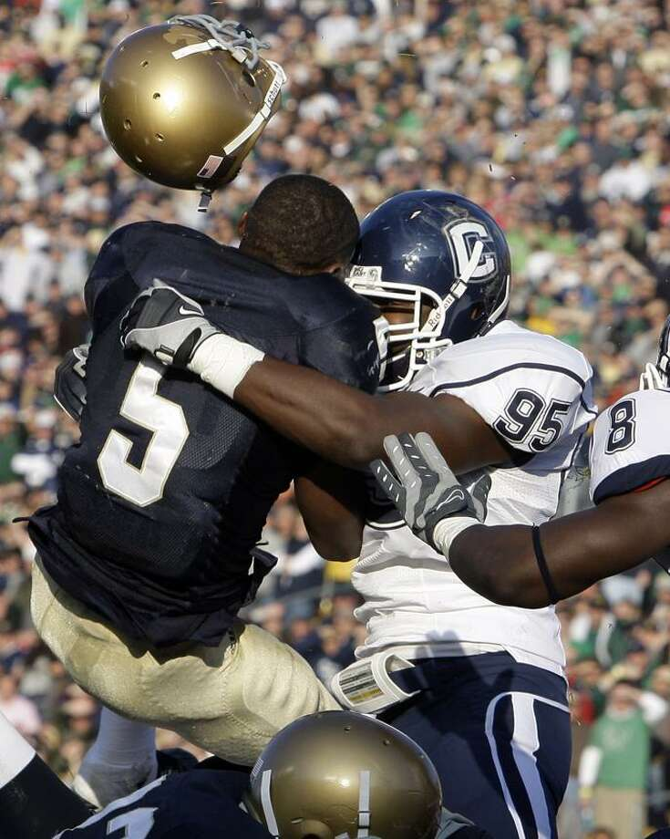 Notre Dame running back Armando Allen Jr., left, looses his helmet as he is hit by Connecticut linebacker Greg Lloyd during the second quarter of an NCAA college football game in South Bend, Ind., Saturday, Nov. 21, 2009. (AP Photo/Michael Conroy) Photo: AP / AP