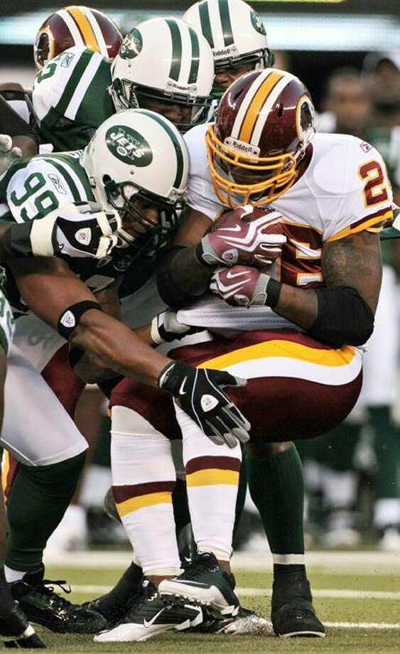 Washington Redskins running back Clinton Portis (26) is tackled by New York Jets linebacker Jason Taylor (99) at New Meadowlands Stadium in East Rutherford, N.J., Friday. (AP Photo/Frank Franklin II) Photo: AP / AP