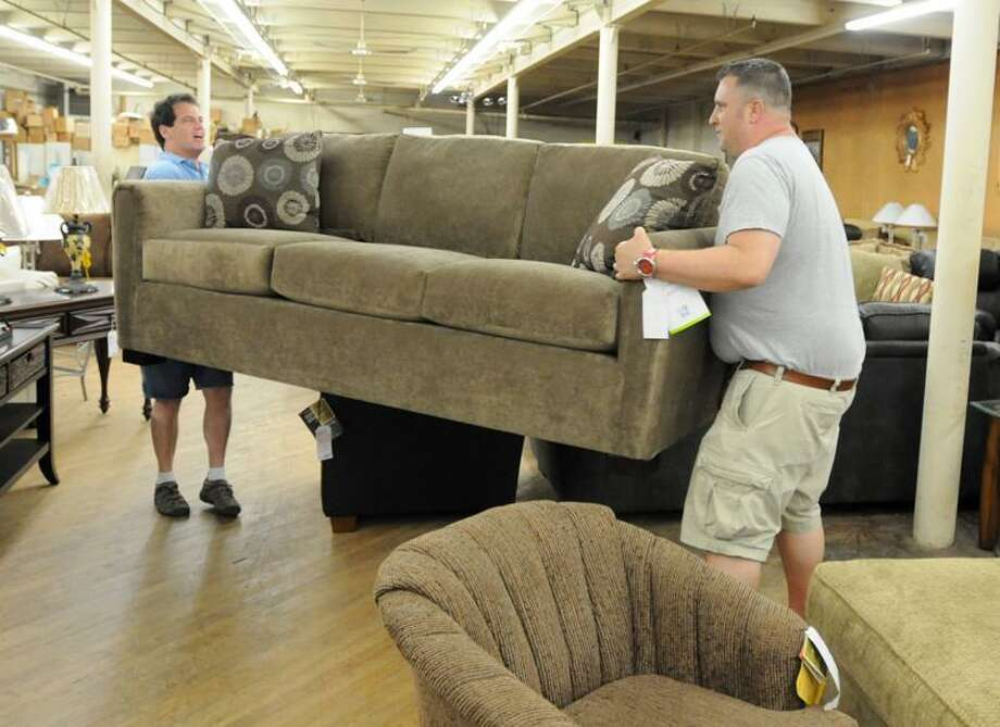 Cary Benjamin, owner of Carroll Cut-Rate Furniture, left, moves a couch with his sales manager, Dave Price, in the showroom of the West Haven store Friday. (Peter Hvizdak/Register)