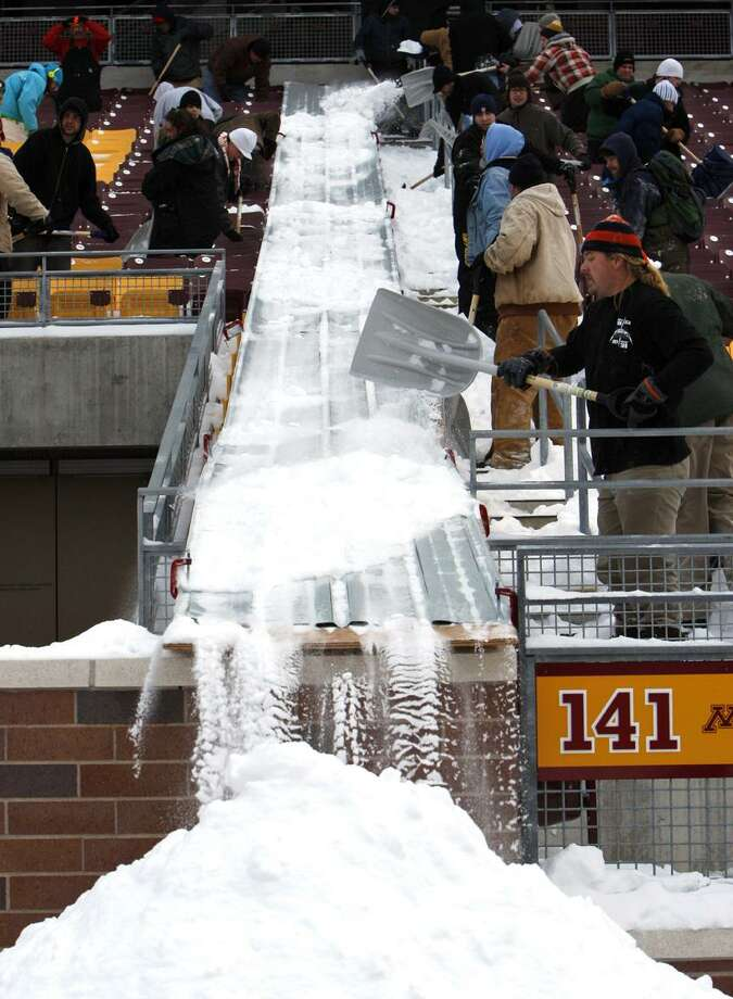 Workers clear snow from TCF Bank Stadium at the University of Minnesota in Minneapolis Wednesday, Dec. 15, 2010.  The inflatable roof of the Metrodome collapsed Sunday after a snowstorm that dumped 17 inches on Minneapolis and will not be repaired in time for Monday night's game, so the Minnesota Vikings will host the Chicago Bears at the TCF Stadium. (AP Photo/Ann Heisenfelt)